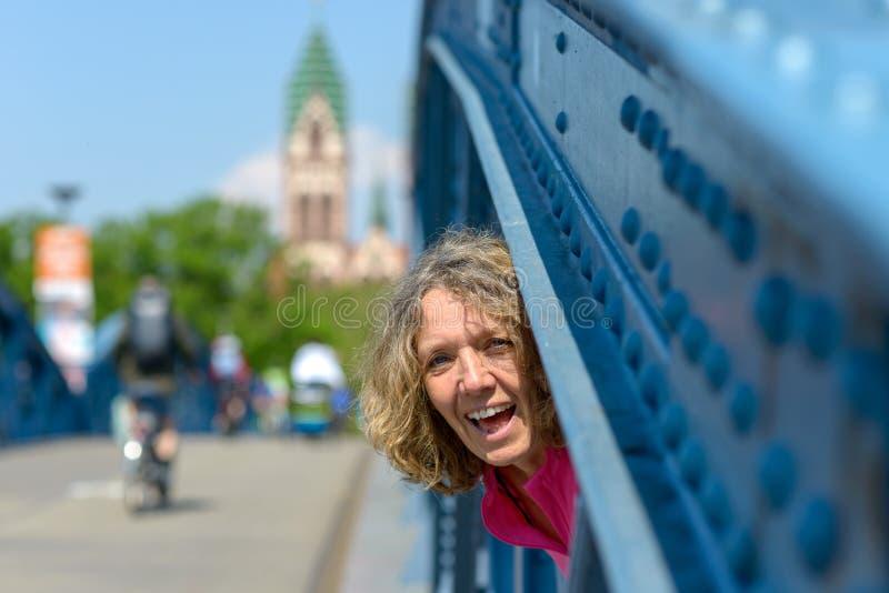 Skämtsam skratta kvinna som plirar till och med en bro arkivfoto