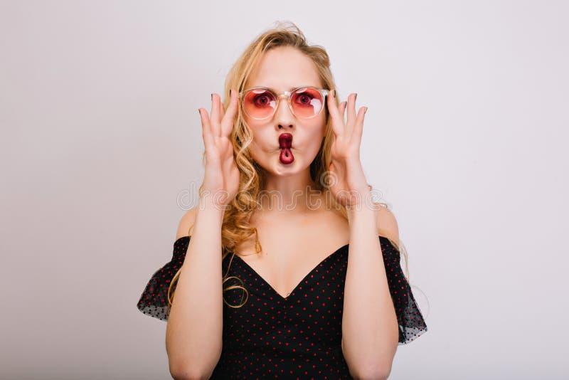 Skämtsam ung blondin med röda kanter som gör fiskframsidan, ung kvinna som har gyckel och att vara galet Bärande rosa stilfulla e fotografering för bildbyråer