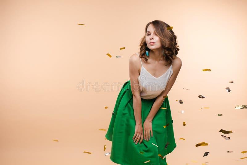Skämtsam ung elegant le kvinna som poserar med styckvattenmelongodisen på studiobakgrund arkivbild