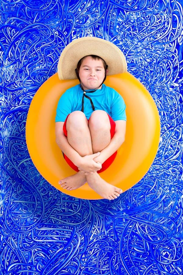 Skämtsam ung pojke i en sommarsimbassäng arkivfoto