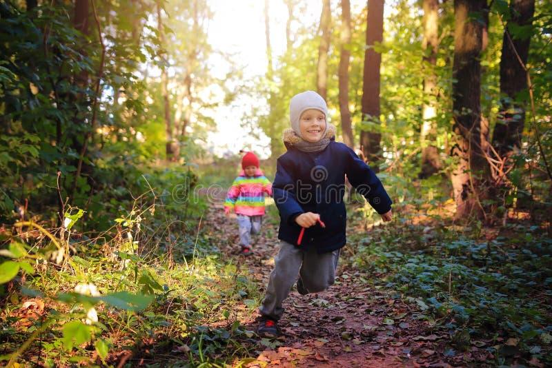 Skämtsamma barn fångar upp med de parkerar in Lås för barnlek upp leken pysen och flickan kör i skog royaltyfria bilder
