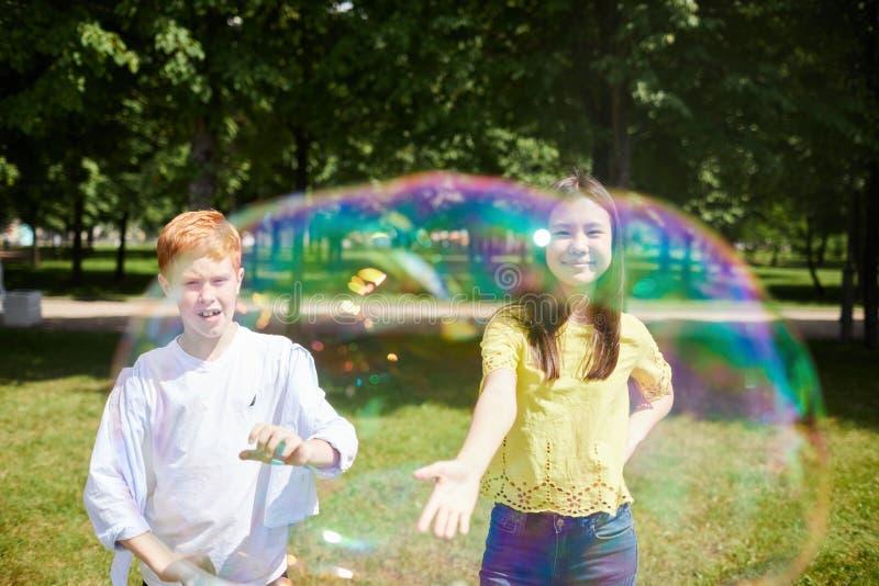 Skämtsamma barn som fångar såpbubblor arkivfoton