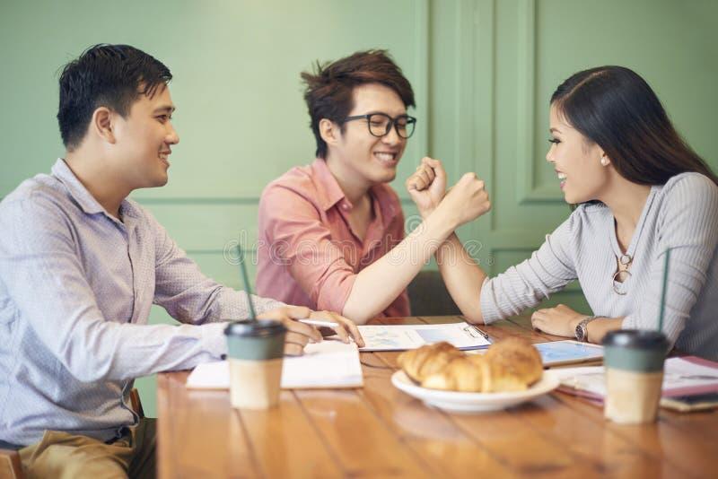 Skämtsamma lyckliga kollegor på kaffeavbrott arkivfoto