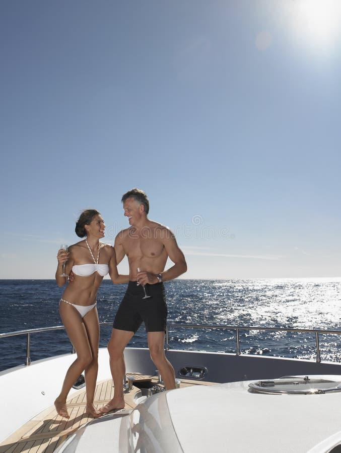 Skämtsamma par som tycker om på yachten arkivfoto