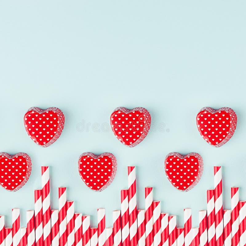 Skämtsamma röda hjärtor och sugrör som gränsen på bakgrund för pastellfärgad färg för modemintkaramell, fyrkant fotografering för bildbyråer