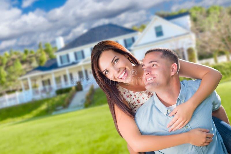 Skämtsamma unga militära par utanför ett härligt nytt hem royaltyfria foton