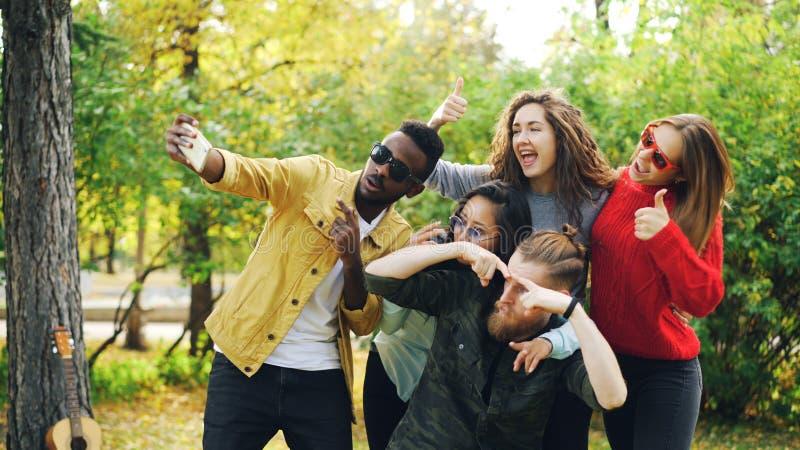 Skämtsamma ungdommän och kvinnor tar selfie parkerar in genom att använda smartphonen, göra roliga framsidor och bära solglasögon arkivfoton