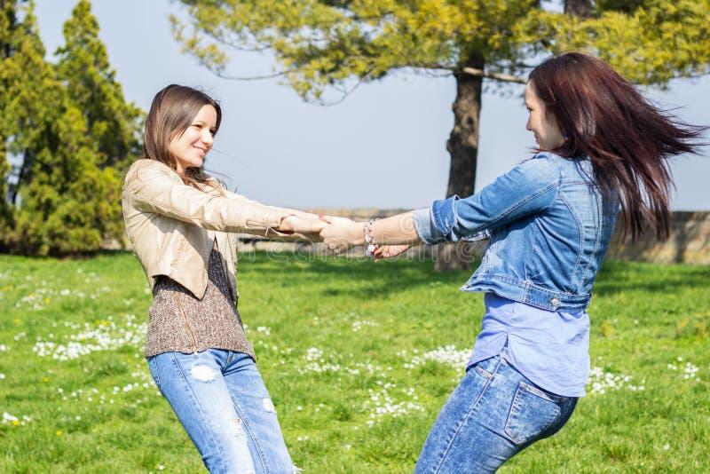 Skämtsamma vänner som rymmer händer och rotera i cirklar royaltyfri foto