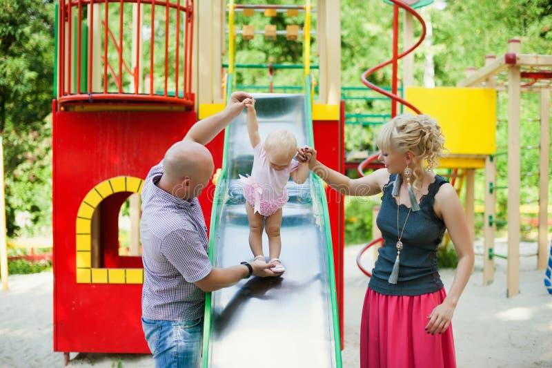 Skämtsamt barn med föräldrar på den utomhus- lekplatsen royaltyfri fotografi
