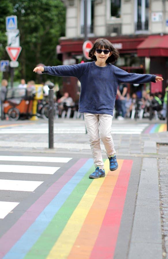 Skämtsamt barn med solglasögon som balanserar armar, i att gå rolig övergångsställe royaltyfria foton