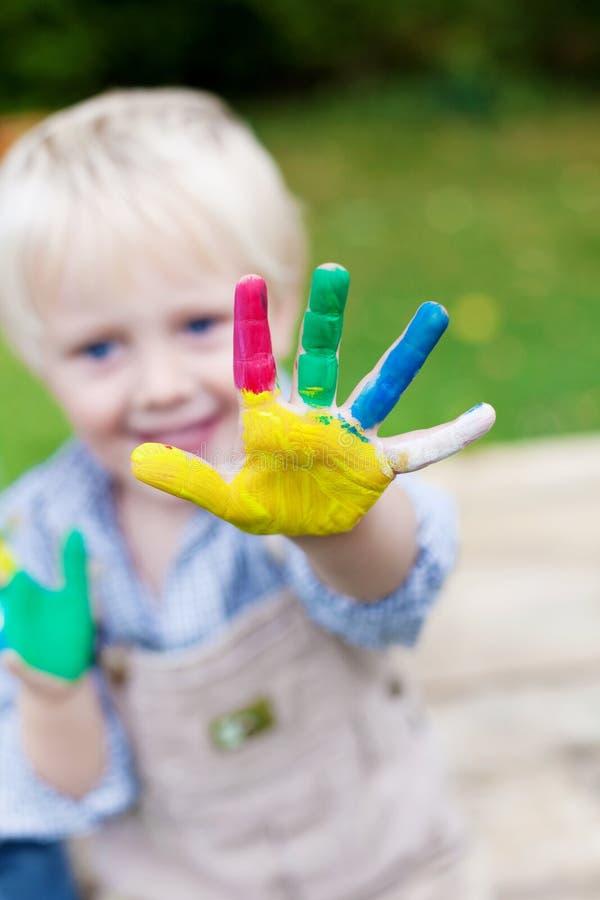 Skämtsamt barn som visar den färgrika handen arkivbilder