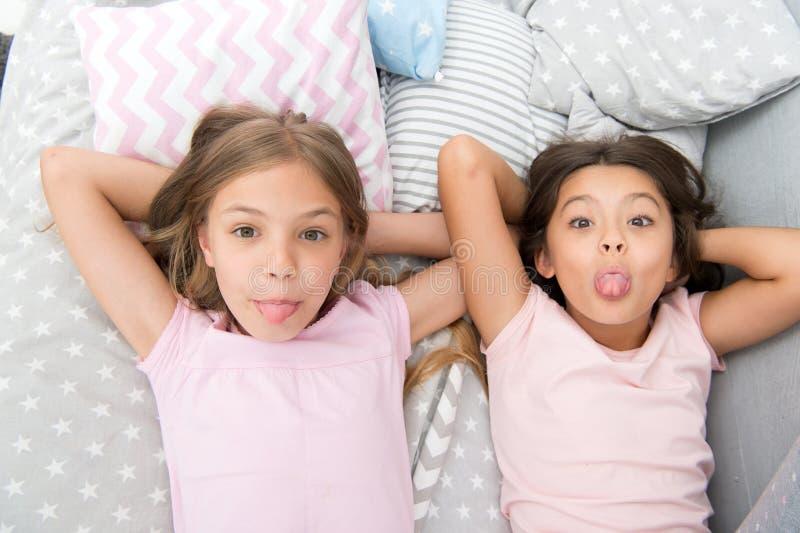 Skämtsamt gladlynt lynne för barn som har roligt tillsammans Pajamaparti och kamratskap Lyckliga små ungar för systrar som in kop royaltyfri bild