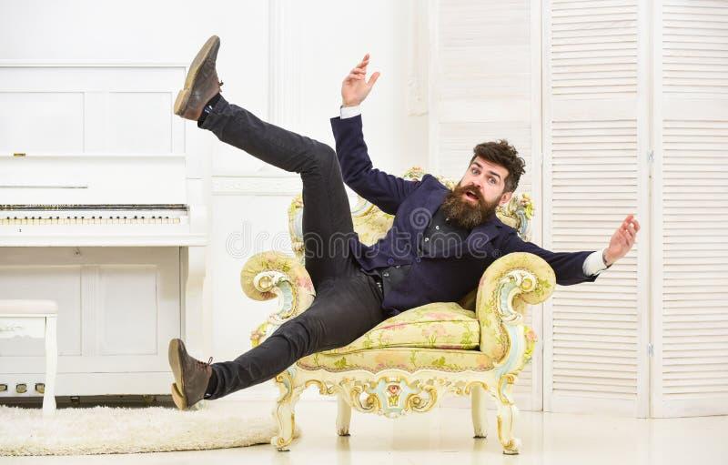 Skämtsamt lynnebegrepp Mannen med skägget och mustaschen som bär den trendiga klassiska dräkten, sitter, hoppar på gammalmodigt arkivfoto