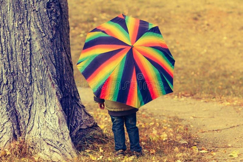 Skämtsamt nederlag för litet barn bak det färgrika paraplyet royaltyfri fotografi