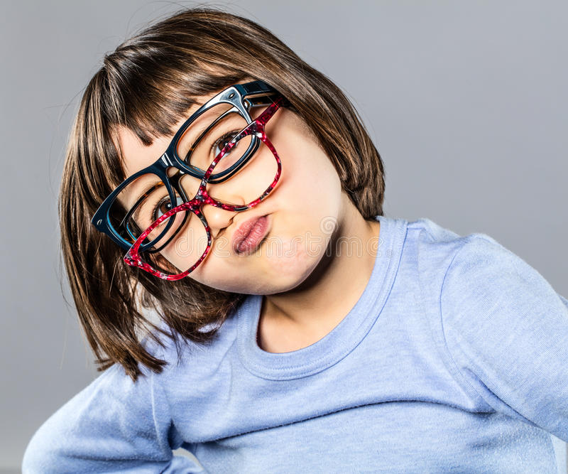 Skämtsamt ungt barn som försöker flera glasögon som trutar och tvekar arkivbild