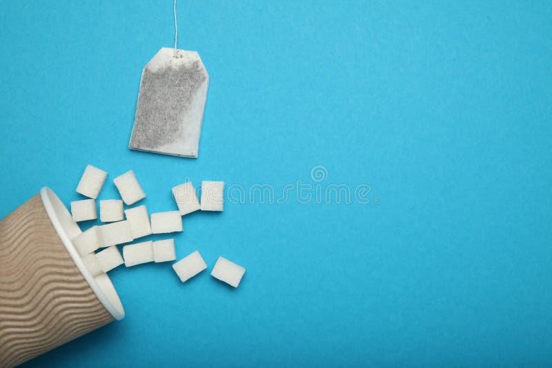 Skära i tärningar vitt socker och tepåsen, sötningsmedelenergidrink Kopiera utrymme f?r text royaltyfri bild