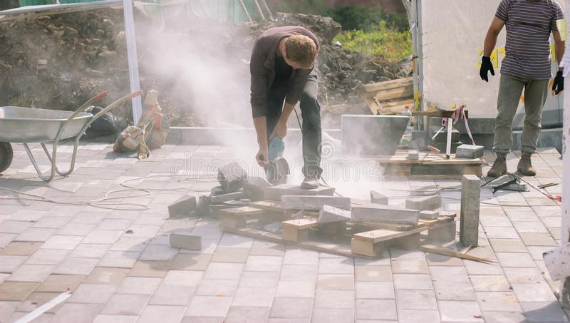 Skäraren för betong för byggnadsarbetarebrukselkraften klippte en sten royaltyfria foton