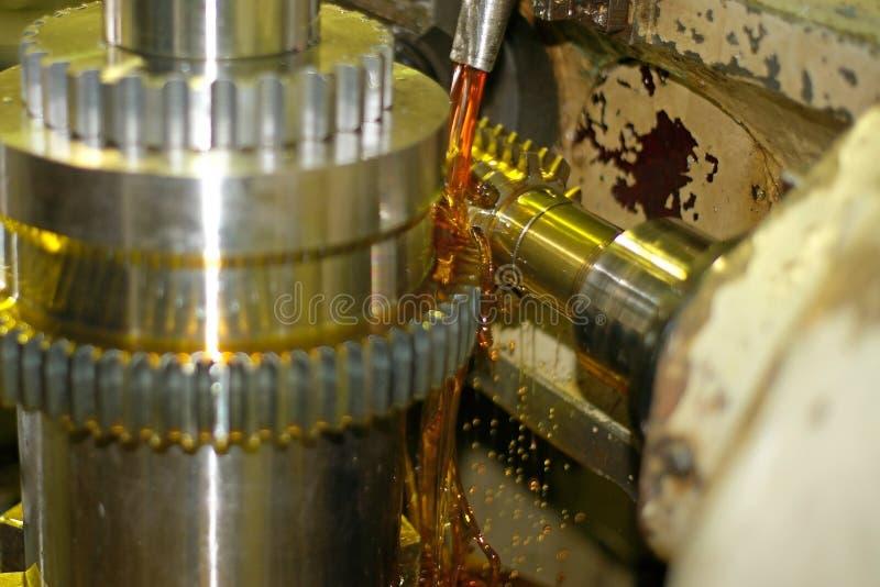 Skäraren reglerar metall, och olja flödar från journalerna för att kyla och smörjning Branschen av metalworking, genom att klippa fotografering för bildbyråer
