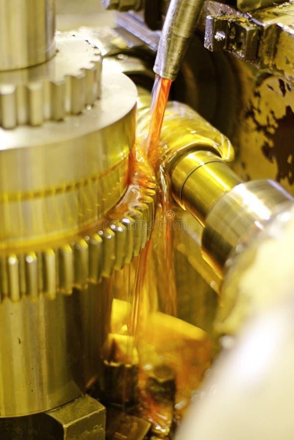 Skäraren reglerar metall, och olja flödar från journalerna för att kyla och smörjning Branschen av metalworking, genom att klippa royaltyfri fotografi