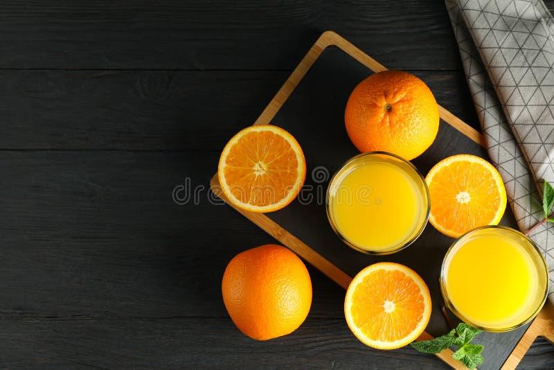 Skärbräda med orange fruktsaft, mintkaramell och apelsiner och kökshandduk på träbakgrund, bästa sikt och utrymme för text arkivfoton