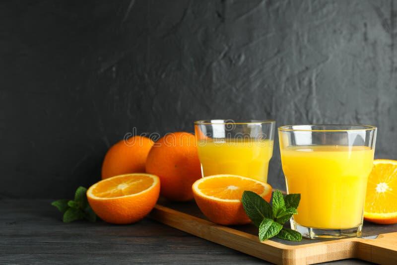 Skärbräda med orange fruktsaft, mintkaramellen och apelsiner på trätabellen mot svart bakgrund, utrymme för text royaltyfri bild