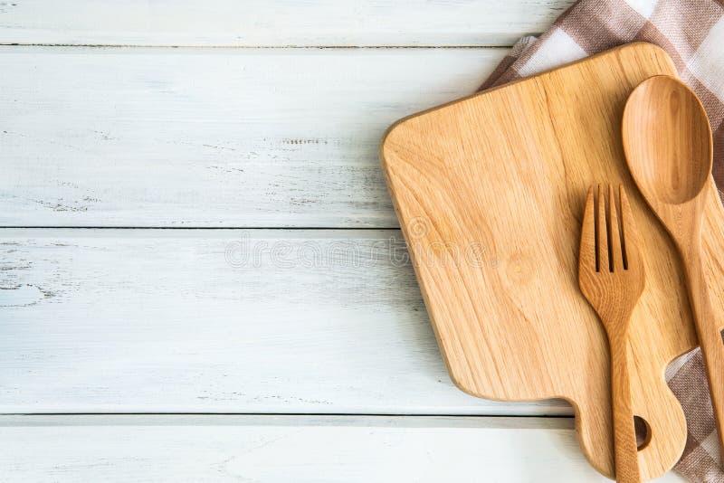 skärbräda med trägaffeln och sked på den vita tabellen, receptmat för sunt begrepp för bakgrund för vanaskottanmärkning arkivfoton
