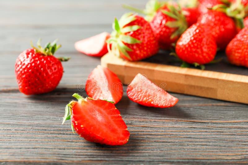 Skärbräda och nya jordgubbar på den trätabellen, closeupen och utrymme för text Frukter f?r sommars?tsak arkivbild