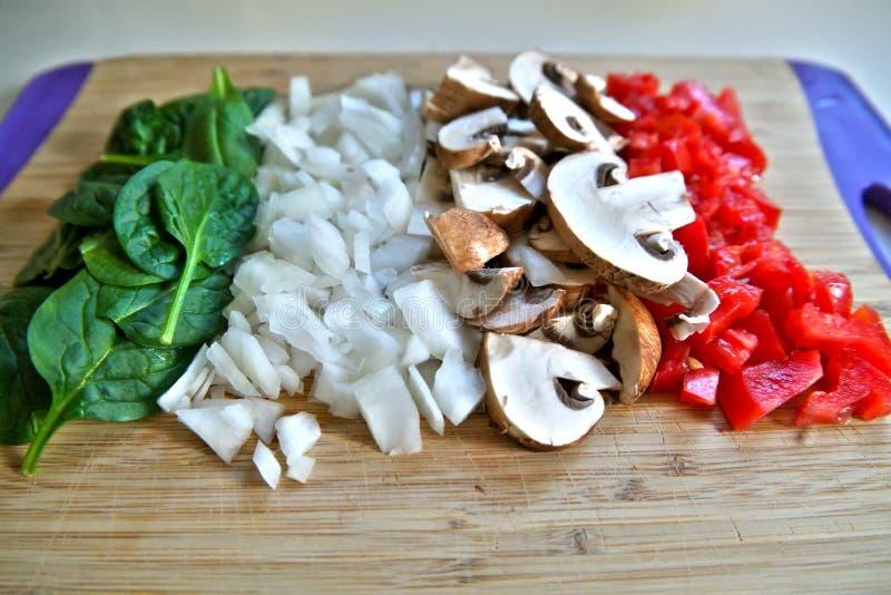 Skärbrädagrönsaker som förbereds för att laga mat royaltyfri bild