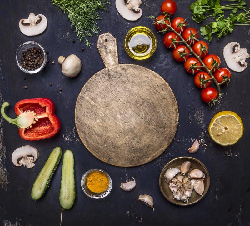Skärbrädan runt om lögningrediensvariation av grönsaker och frukter, stället för text, inramar bästa sikt för trälantlig bakgrund arkivbild