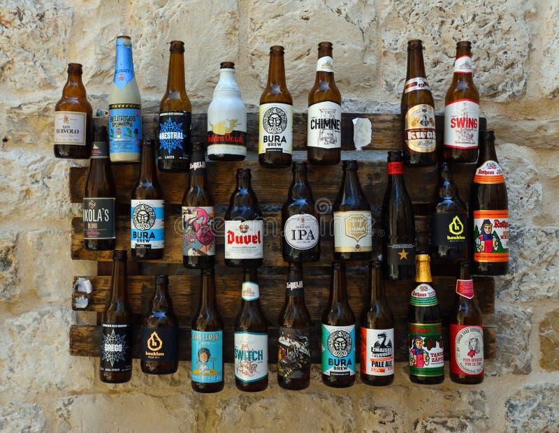 Skärm av ölflaskor på väggen royaltyfria foton