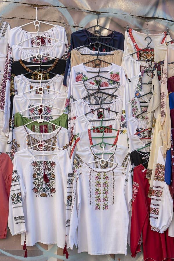Skärm av broderade ukrainska slavic kvinnor och för skjortabroderi för män traditionella kläder i utomhus- loppmarknad i Kiev, Uk royaltyfria bilder