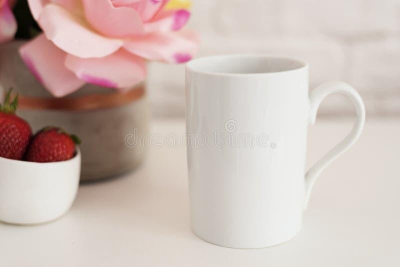 Skärm för kaffekoppprodukt Vit tabell för kaffe Jordgubbar i den guld- bunken, vas med rosa rosor arkivbild
