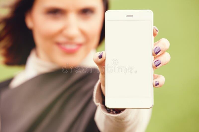 Skärm för kvinnavisningmobiltelefon till kameran arkivfoton