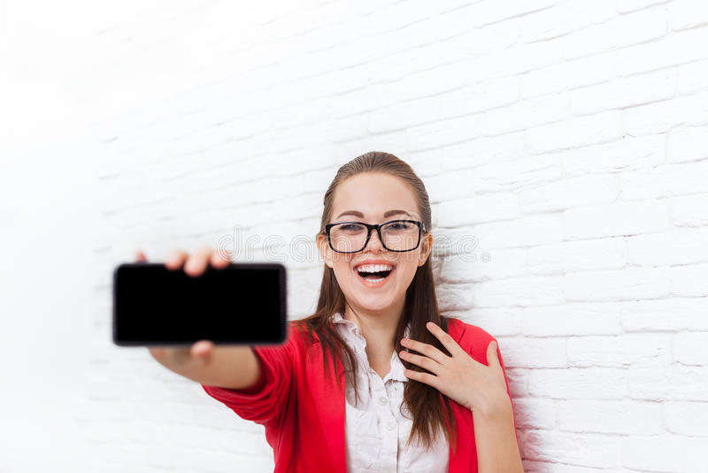Skärm för telefon för affärskvinnashowcell smart med lyckligt leende för tomma för kopieringsutrymmekläder röda exponeringsglas f royaltyfri fotografi