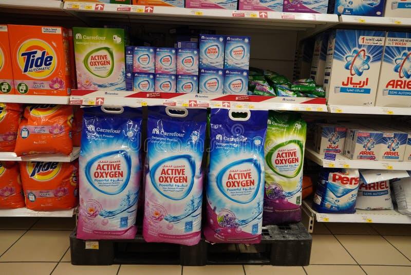 Skärm på stormarknader med olika märken av tvättpulver i lådor Partihandel Tide, Ariel, Omo tvättmedelsfacken är klädda uppåt royaltyfria foton