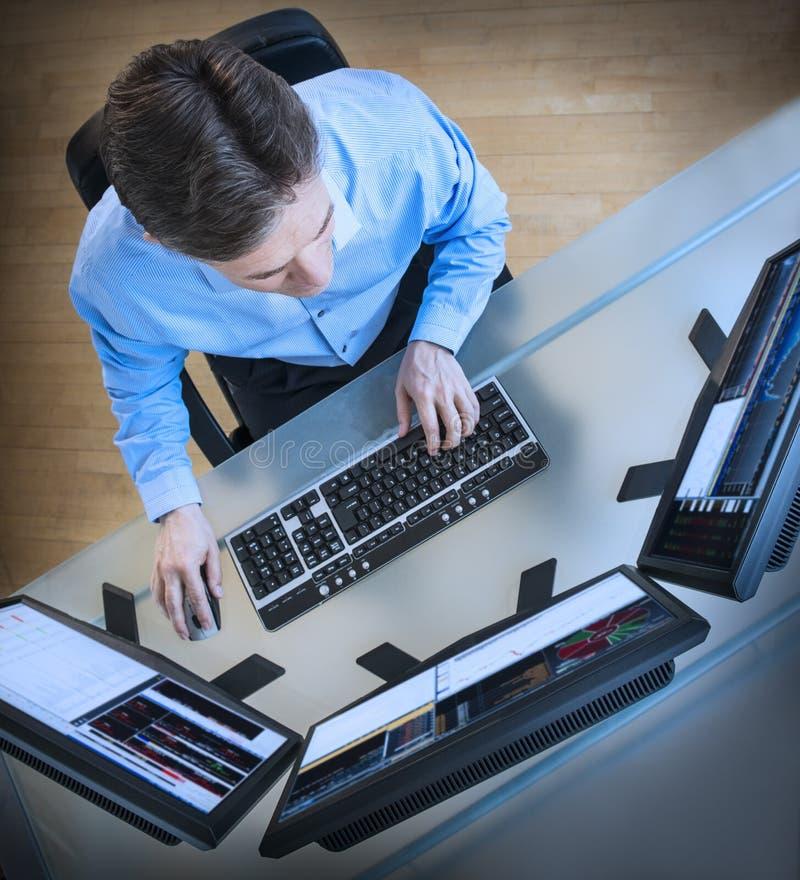 Skärmar för affärsmanAnalyzing Data On multipel på skrivbordet royaltyfri bild
