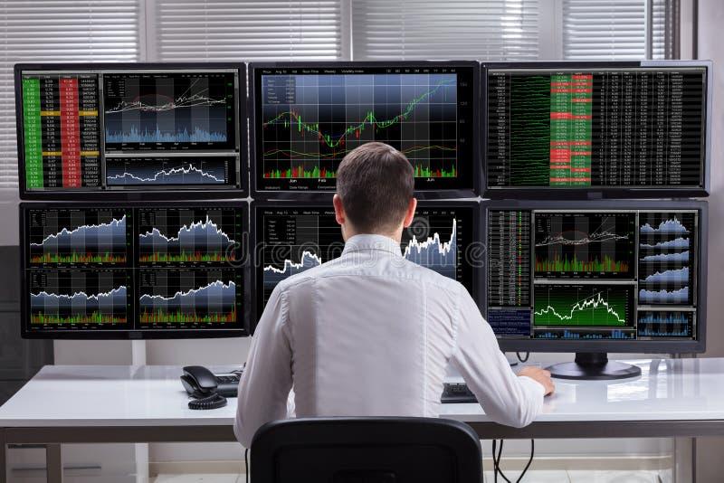 Skärmar för aktiemarknadmäklareAnalyzing Graphs On dator arkivbild