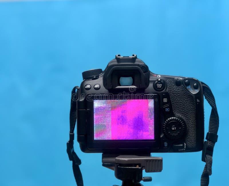 Skärmskärm för DSLR LCD med PIXELtextur av kameramatrisen på en tripod på blå bakgrund royaltyfri bild