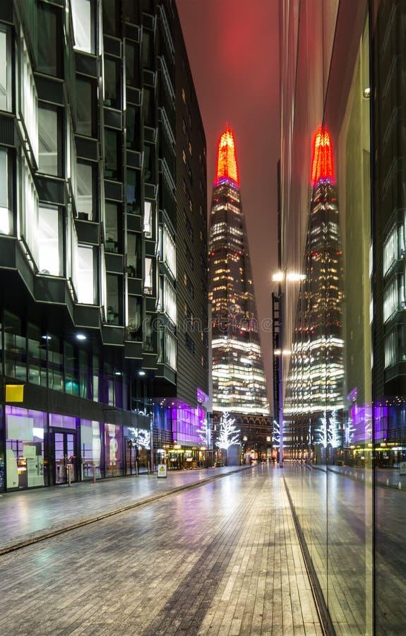 Skärvan mellan kontorsbyggnader på natten royaltyfria bilder