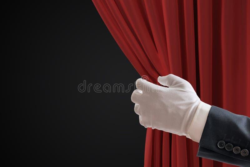 Skådespelaren drar röda gardiner i teater med handen arkivbild