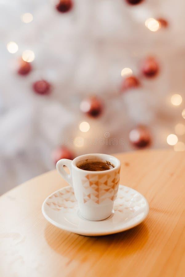 Skåpning av espresso eller kaffe i vit kopp i fint jularrangemang, festlig dekoration med vit bokeh-bakgrund, kopia arkivfoto