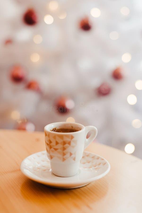 Skåpning av espresso eller kaffe i vit kopp i fint jularrangemang, festlig dekoration med vit bokeh-bakgrund, kopia fotografering för bildbyråer
