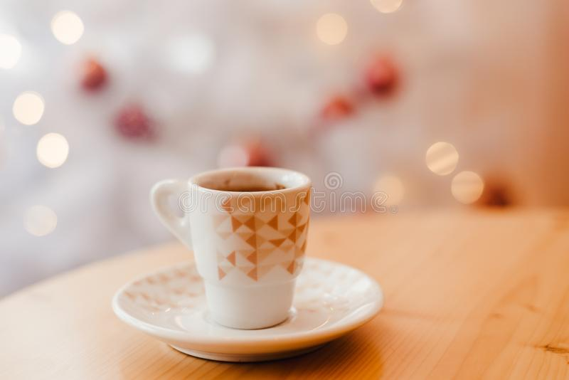Skåpning av espresso eller kaffe i vit kopp i fint jularrangemang, festlig dekoration med vit bokeh-bakgrund, kopia royaltyfria foton
