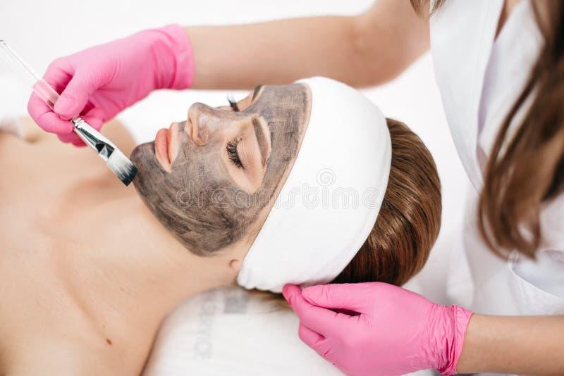 Skóra kosmetyki i opieka Beautician stosuje czarną maskę z muśnięciem na pięknej żeńskiej twarzy przygotowujemy się zdjęcia royalty free