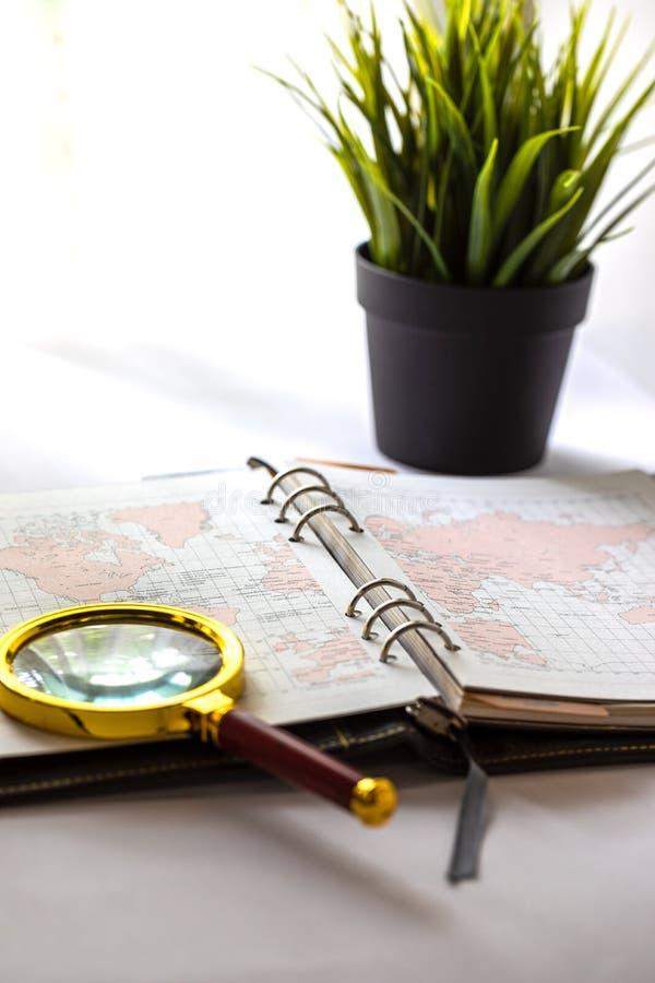 Skóra ringowy planista otwarty dla przedstawienia na mapy stronie na białym workspace z złotymi powiększać - szklanymi i małymi t obraz stock