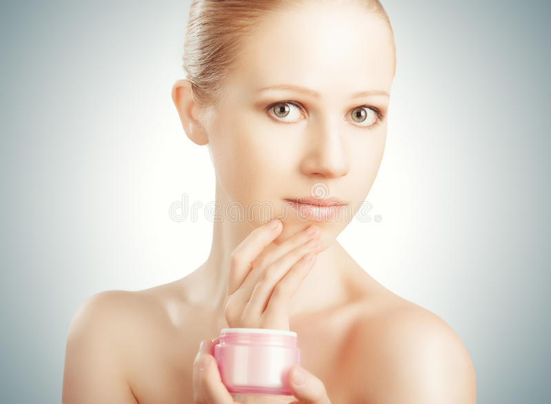 Skóry opieka. szczęśliwego piękna zdrowa dziewczyna z słojem śmietanka zdjęcie stock