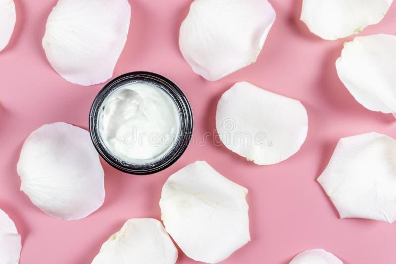 Skóry opieki śmietanki i biel róży płatki na różowym tle Odgórny widok zdjęcie stock