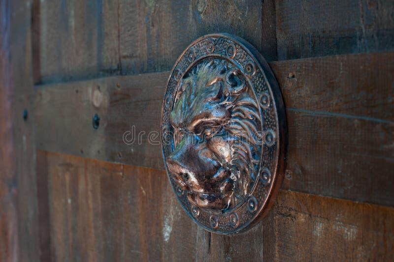 Sköld i form av en kopia av den falska Roman Lion på träportar Höger sikt royaltyfria bilder