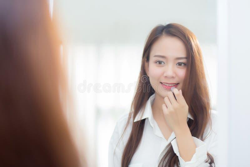 Skönhet av ståenden av den unga asiatiska kvinnan på spegeln som rymmer och ser en makeupläppstift royaltyfria bilder