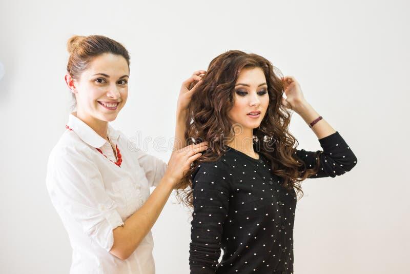 Skönhet-, frisyr- och folkbegrepp - lycklig ung kvinna med den fulländande frisyren för frisör på salongen fotografering för bildbyråer